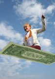 Flying economy. Girl flying af magic carpet made from a giant dollar bill Stock Images