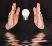 Flying electrical bulb between palms Royalty Free Stock Photo