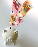 Flying Euro banknotes with white piigy bank Royalty Free Stock Photography