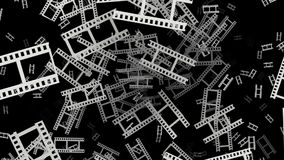 Flying film tape fragments in white on black. In backgrounds stock video footage