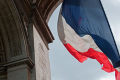 Flying the flag. French flag fluttering in the wind from the Arc de Triomphe. The Arc de Triomphe built in 1806. Central area known as Place Charles de Gaulle Royalty Free Stock Image