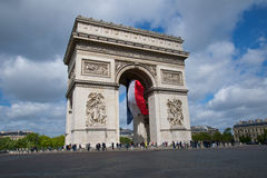 Flying the flag. French flag fluttering in the wind from the Arc de Triomphe. The Arc de Triomphe built in 1806. Central area known as Place Charles de Gaulle Royalty Free Stock Images