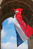 Flying the flag. French flag fluttering in the wind from the Arc de Triomphe. The Arc de Triomphe built in 1806. Central area known as Place Charles de Gaulle Royalty Free Stock Photography