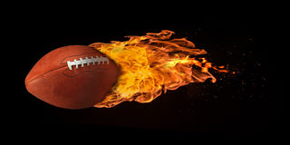 Flying Football Engulfed in Flames. Flying football engulfed in trailing flames with sparks flying on a black background. Concept of a fiery competition or fast Stock Image