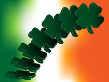 Flying Four Leaf Clovers over Irish Flag Stock Photography