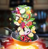 Flying fresh vegetables and spices falling into a pan. royalty free stock photo