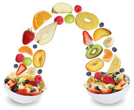 Flying fruit salad in bowl with fruits like apples, oranges, pea Royalty Free Stock Photos