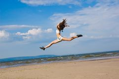 Flying girl. Young woman jumping alone on the beach Royalty Free Stock Photos