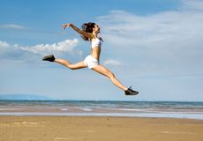 Flying girl. Young woman making exercise on the beach Stock Photography
