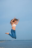 Flying girl. Beautiful young girl frozen in mid-air on blue sky background Royalty Free Stock Photos