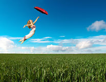 Flying girl with red umbrella Stock Images