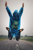 Flying girl. Women wear rainwear jumping on the road at the time of rain Stock Photo