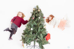 Flying girls decorating Christmas tree, dressed in sweater Royalty Free Stock Photography