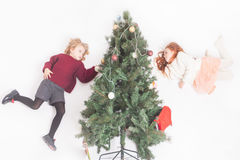 Flying girls decorating Christmas tree, dressed in sweater Royalty Free Stock Image