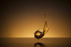 Flying glass of whiskey. Falling glass from which spill whiskey on a gold background Stock Photo