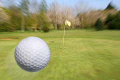 Flying golf ball. Golf ball flying to the cup. Zooming to the hole Royalty Free Stock Image
