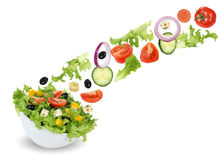 Flying green salad in bowl with tomatoes, onion, olives and cucu Stock Photos