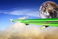 Flying greener. Globe with green airplane wing flying over a tropical cloudscape. Metaphor or concept of energy conservation and more efficient flying in the Stock Photos