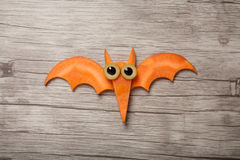 Flying Halloween bat made of carrot. On board Stock Photography