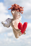 Flying Happy Angel. Flying Happy Angel with Red heart at the blurred clouds background. Soft toy Stock Photos