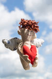 Flying Happy Angel. Flying Happy Angel with Red heart at the blurred clouds background. Soft toy Royalty Free Stock Photos