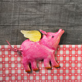Flying happy pink pig on wooden old checked background. royalty free stock photo
