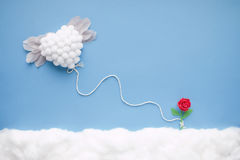 Flying heart. Flying white heart with feather wings, attached by a white string to a tiny handmade red flower, in a heavenly scenery with clouds made of cotton stock image