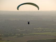 Flying high. Paraglider flying high over countryside stock photography