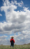 Flying High. Young boy flying a kite high in the beautiful blue sky royalty free stock image