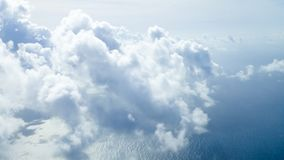 Flying high above the clouds over the Atlantic. Big blue ocean with big fluffy white clouds and blue skies stock images
