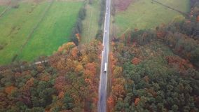 Flying high above container semi truck transporting goods on highway across the country in beautiful autumn evening. Traffic drivi. Ng and speeding on busy stock video footage