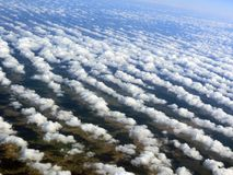 Flying high above the ground, below the beautiful clouds and the earth is visible stock images
