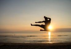 Flying high kick at sunrise. Martial arts master at sunrise Stock Images