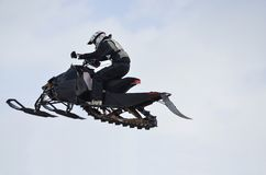 Flying high on a snowmobile rider against the sky Stock Photo