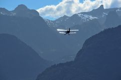 Flying into the hills. An Antonov A-2 bi-plane flying into the alps. In the far distance a small single winged passenger plane can also be made out Royalty Free Stock Image