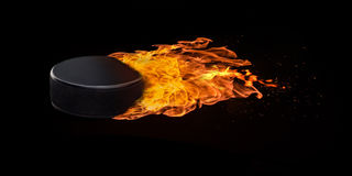 Flying Hockey Puck Engulfed in Flames. Flying hockey puck engulfed in trailing flames with sparks flying on a black background. Concept of a fiery competition or Stock Photography