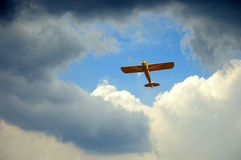 Flying In The Hole. A piper airplane appears through the hole in the clouds on a stormy day Stock Photography