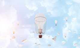 Flying hot air balloons in the air. Colorful aerostats flying among paper planes and over the blue cloudy sky. 3D rendering Royalty Free Stock Photos