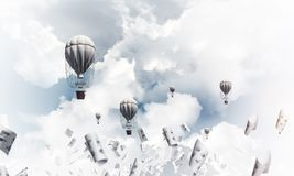 Flying hot air balloons in the air. Colorful aerostats flying among paper documents and over the blue cloudy sky. 3D rendering Royalty Free Stock Images