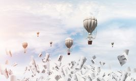 Flying hot air balloons in the air. Colorful aerostats flying among paper documents and over the blue cloudy sky. 3D rendering Stock Photos