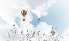 Flying hot air balloons in the air. Colorful aerostats flying among paper documents and over the blue cloudy sky. 3D rendering Stock Photography