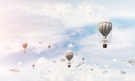 Flying hot air balloons in the air. Colorful aerostats flying among paper planes and over the blue cloudy sky. 3D rendering Stock Photography