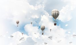Flying hot air balloons in the air. Colorful aerostats flying among paper planes and over the blue cloudy sky. 3D rendering Stock Photos