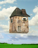 Flying house. Fantasy background of an inventive-collage house that flying with lawn and sky with clouds on the background Stock Photography