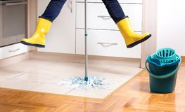 Flying housekeeper mopping floor. Flying maid in gumboots mopping tiled floor in kitchen. Woman multitasking and speed in housekeeping chores Stock Images