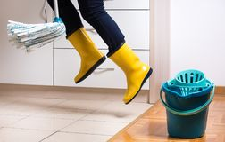 Flying housekeeper mopping floor. Flying maid in gumboots mopping tiled floor in kitchen. Woman multitasking and speed in housekeeping chores Stock Photos