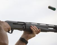 Flying hull. Empty shotshell after ejection from a semi auto shotgun Royalty Free Stock Photo