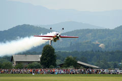 Flying inverted with lots of smoke. Airshow performer is flying inverted near the crowd Stock Photography
