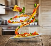 Flying Italian pasta with ingredients. Flying Italian spaghetti pasta with ingredients. Concept of low gravity food. Served on wooden table, blur kitchen Stock Image