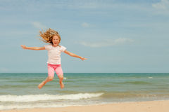 Flying jump beach girl on blue sea shore Stock Photos